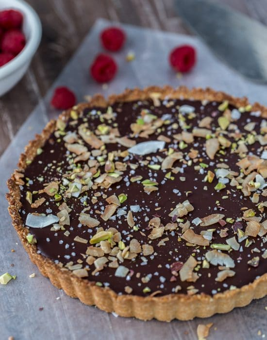 A decadent gluten free and vegan chocolate coconut tart that starts with a chewy coconut almond crust and is filled with creamy chocolate coconut ganache.