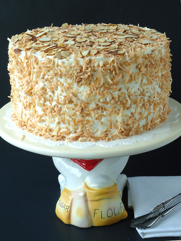 Coconut almond cream cake is a coconut lover's dream cake, and the perfect Easter dessert recipe. Coconut cake is filled with almond cream filling, then topped with fluffy coconut cream cheese frosting! | BlahnikBaker.com
