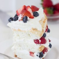 This classic angel food cake recipe is filled with homemade dairy-free coconut whipped cream and studded with berries for a pretty 4th of July look!