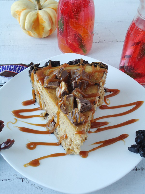 A creamy snickers peanut butter cheesecake recipe with a chocolate oreo crust and brown sugar salted caramel drizzle. Perfect for Halloween!