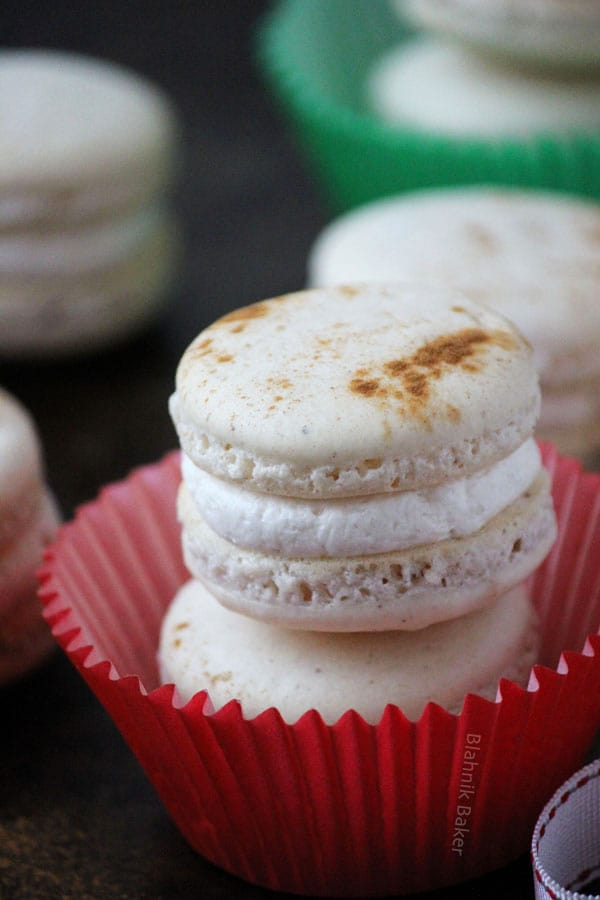Eggnog macarons are perfectly spiced holiday cookies, with hints of cinnamon, cloves and nutmeg, filled with creamy eggnog buttercream.   Recipe on BlahnikBaker.com