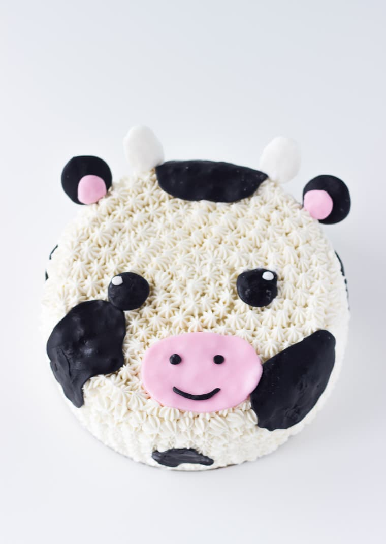 This Cow Cake tutorial makes for an easy and adorable fondant and frosting decorated cow cake; perfect for any cow-themed celebration. Get the recipe on BlahnikBaker.com
