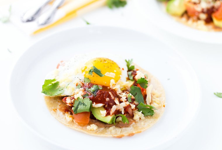 An authentic huevos rancheros recipe with homemade red chile paste, fried eggs and refried beans.