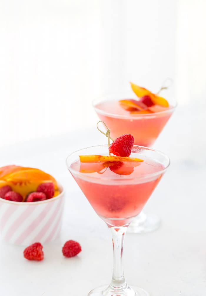 This summer peach raspberry martini recipe is filled with fresh raspberries and juicy peach flavors. A refreshing summer cocktail that's easy to whip up.