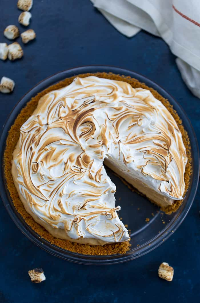 This Peanut Butter S'mores Pie starts with a crunchy graham cracker crust lined with chocolate, a creamy whipped peanut butter filling, and a cloudy marshmallow meringue topping.  #peanutbutterpie #pie #smores #smorespie #recipe #summer #dessert